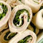 Sliced pinwheel sandwiches in a green container.