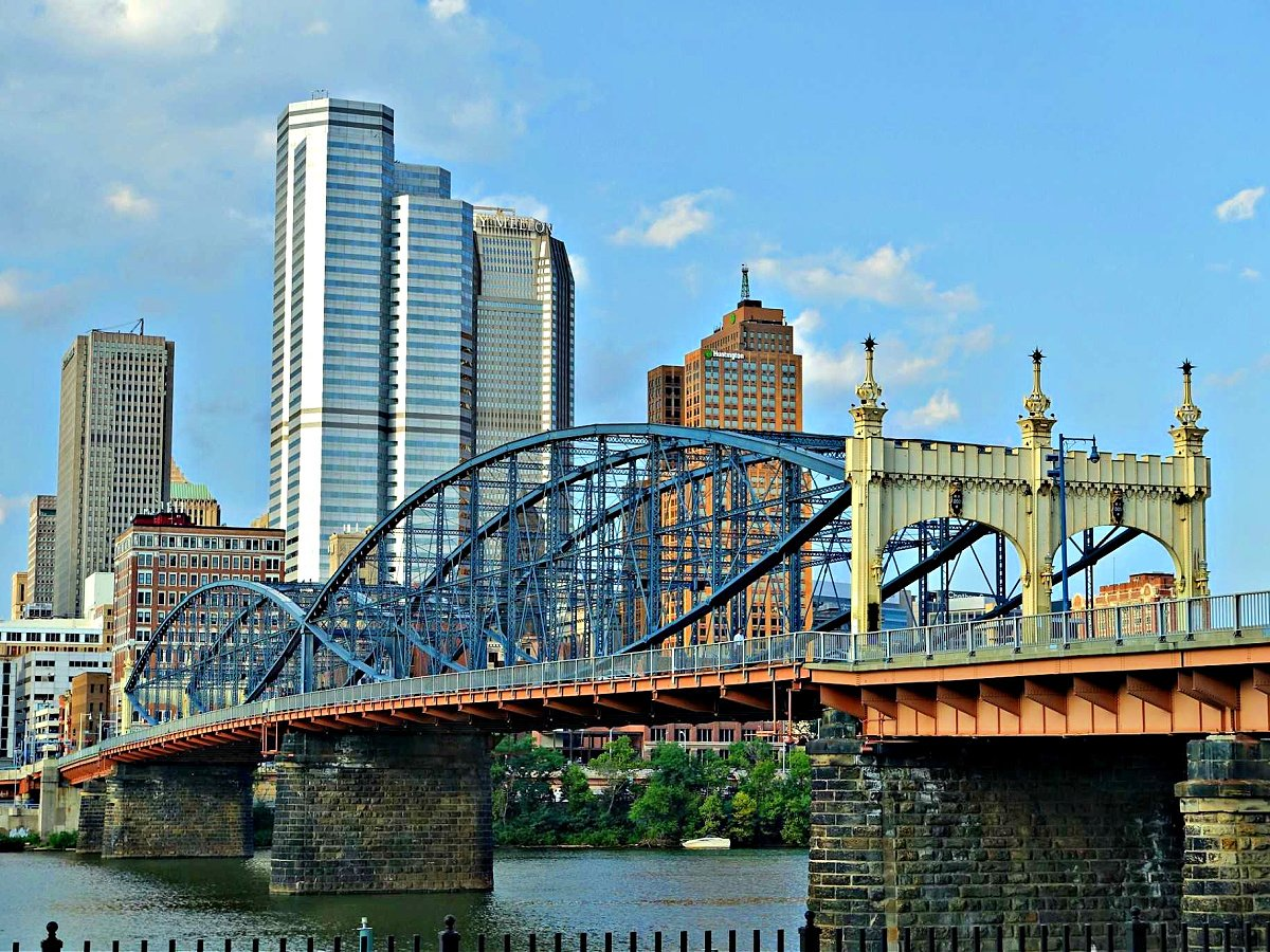 Yellow and blue bridge with Pittsburgh skyline in the background.