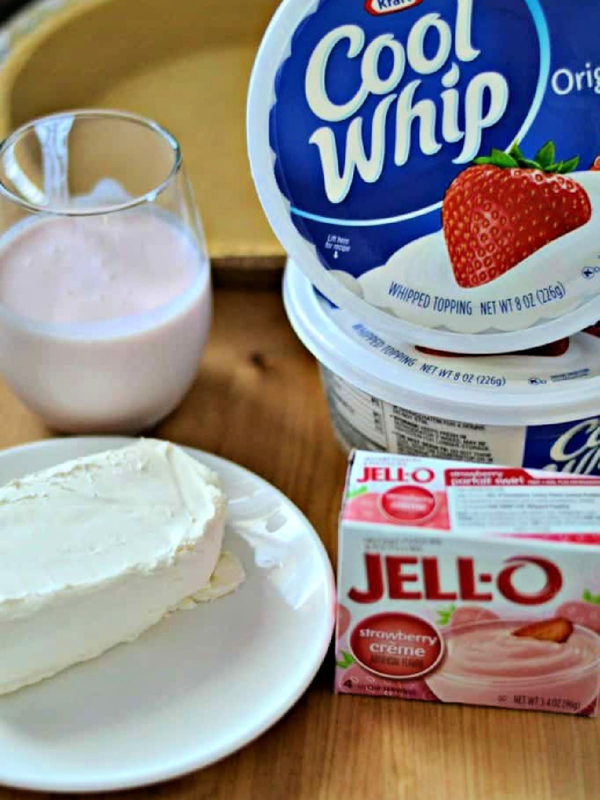 Block of cream cheese, strawberry kefir, strawberry pudding mix, and two containers of Cool Whip on a cutting board.