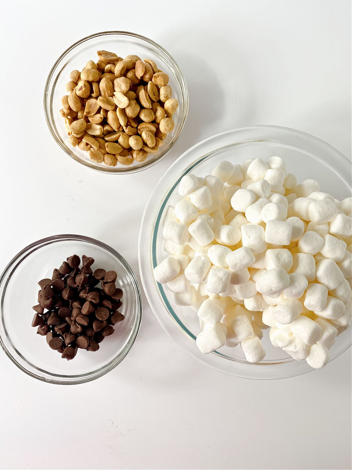 Miniature marshmallows, chocolate chips, and peanuts in glass bowls.