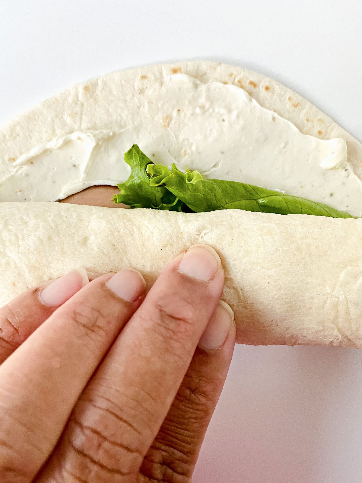 Woman's hand rolling a tortilla sandwich with cream cheese, turkey, and lettuce.