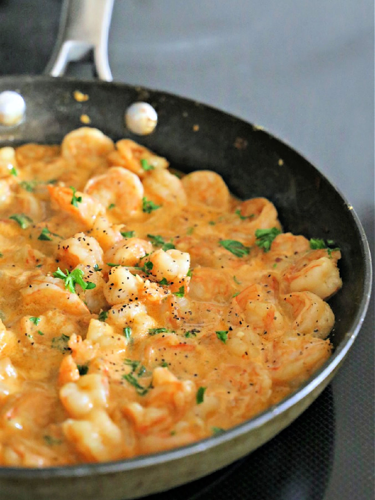 Non-stick skillet with shrimp scampi garnished with parsley.