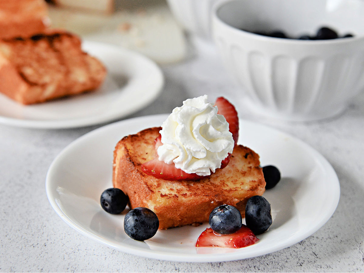 Slice of toasted angel food cake topped with berries and whipped cream on a white plate.