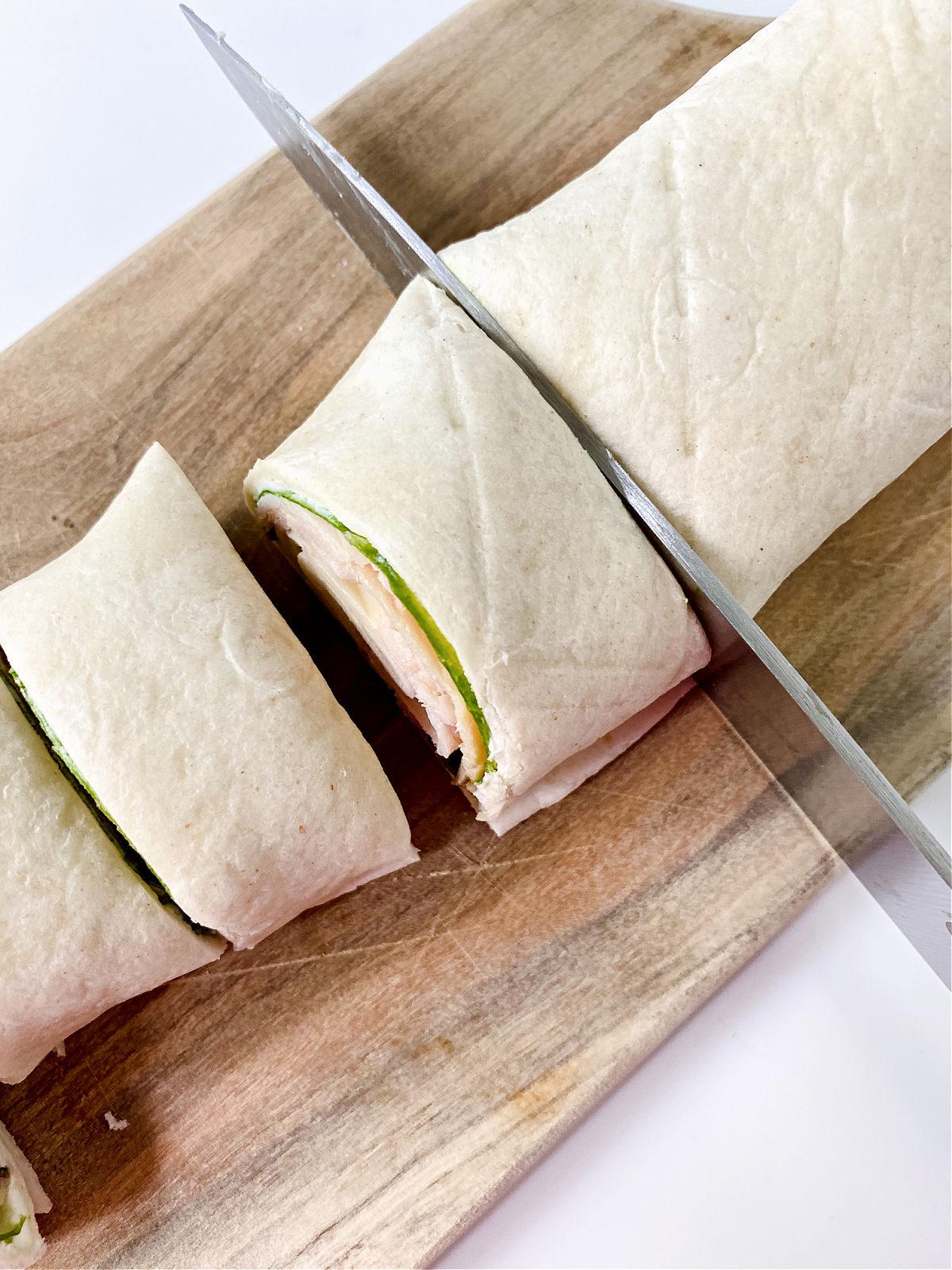 Knife cutting through a rolled pinwheel sandwich.