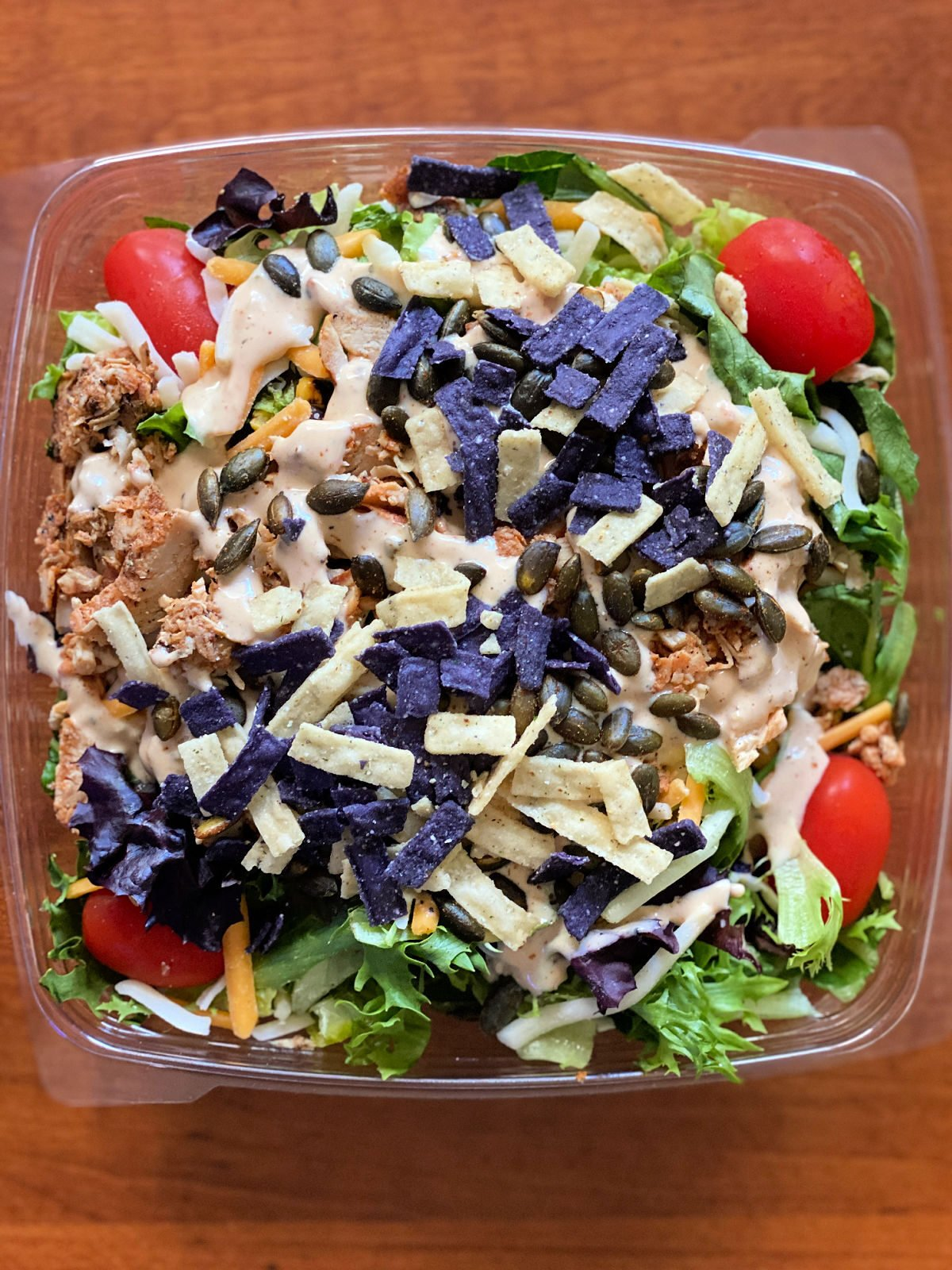 Chick-Fil-A's Southwest Salad topped with tortilla chips and salad dressing.