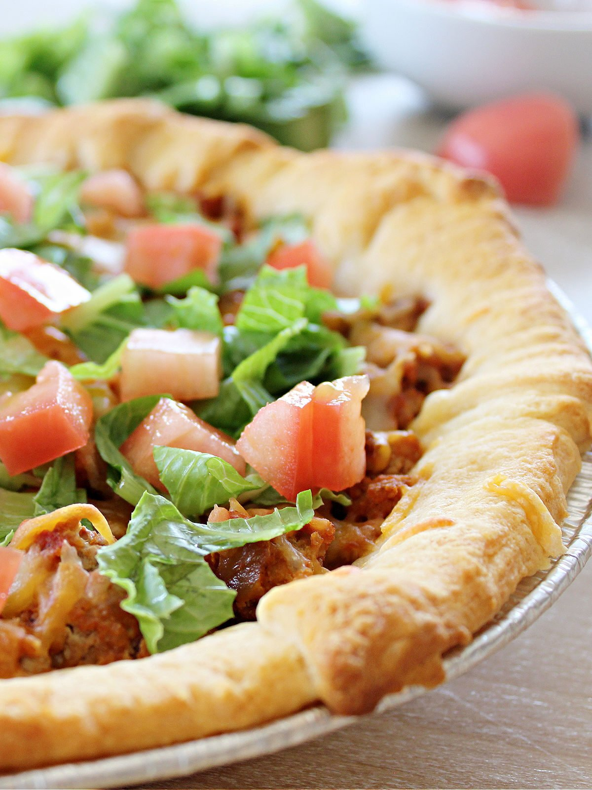 Taco pie made with ground beef and topped with layer of cheese and lettuce and tomatoes.