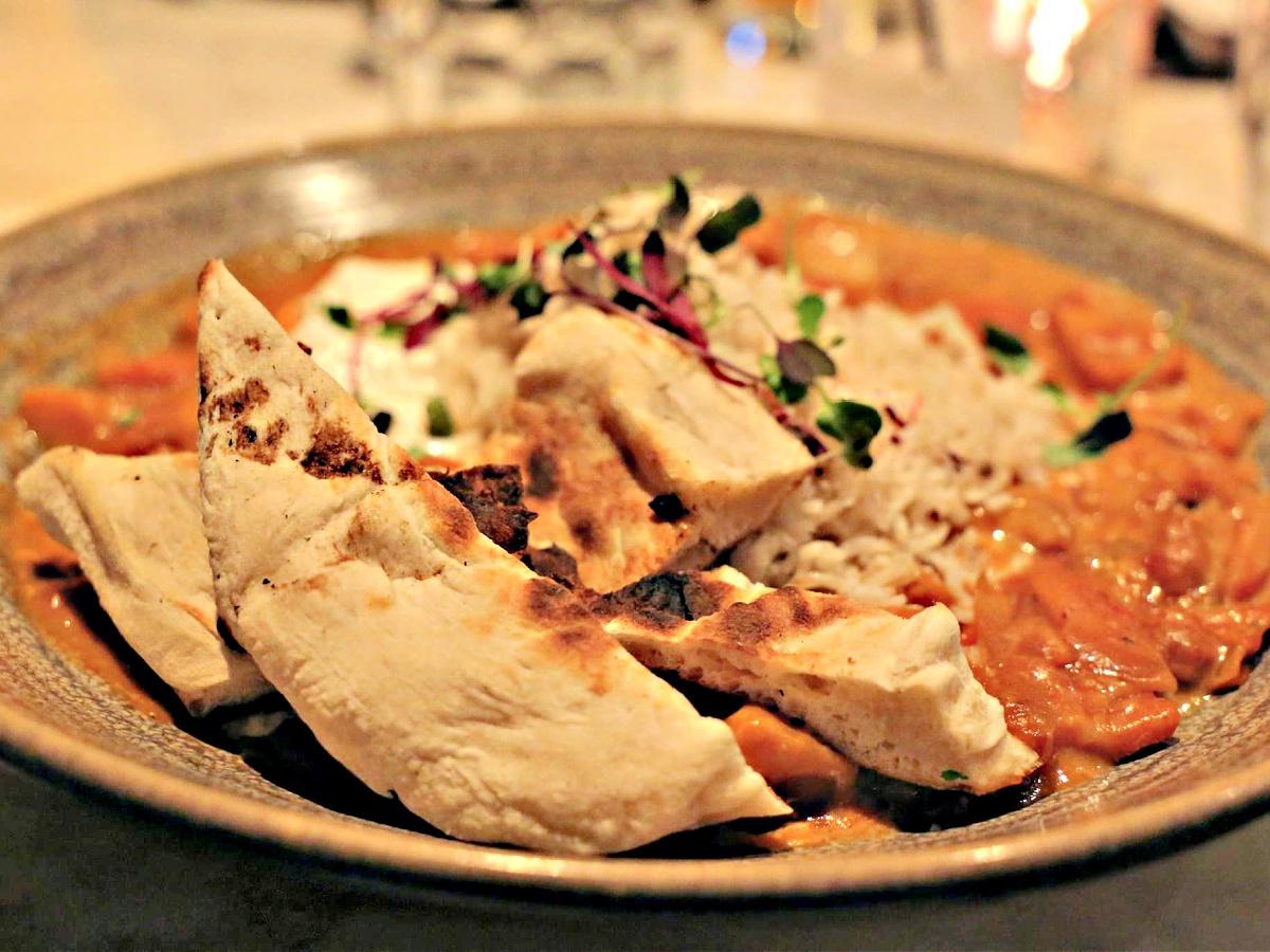 Plate of Vegetarian Tikka Masala served with naan.