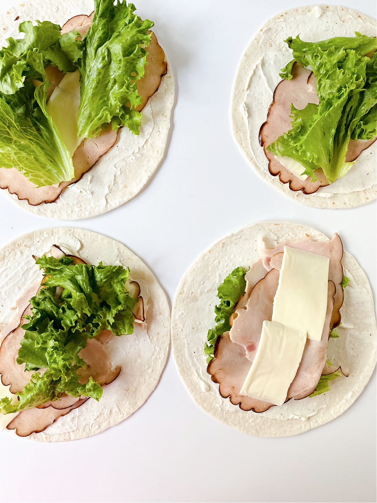 Four tortillas topped with seasoned cream cheese, turkey, lettuce, and cheese.