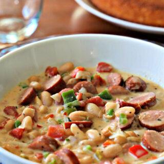 White soup bowl with cajun chili and cornbread.