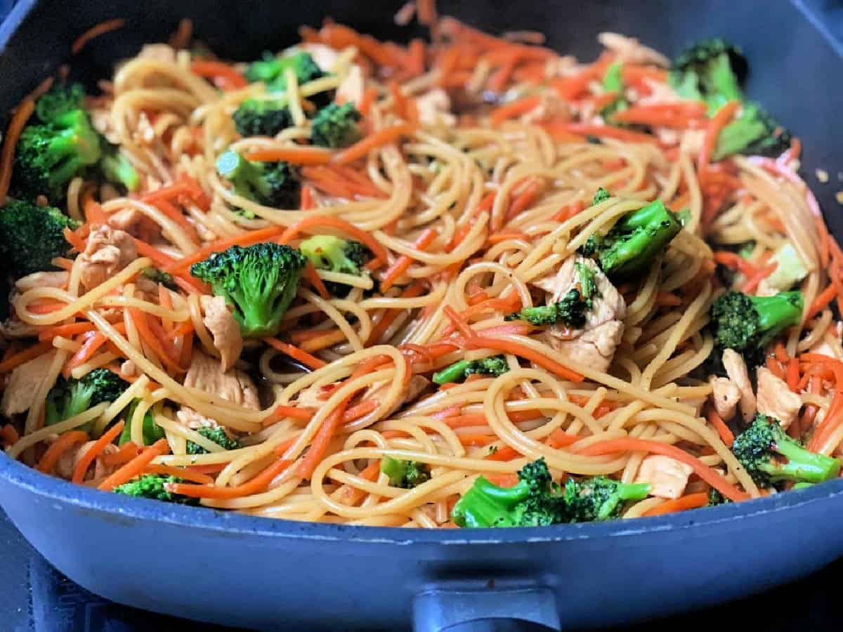 Chicken lo mein with broccoli in a non-stick skillet.