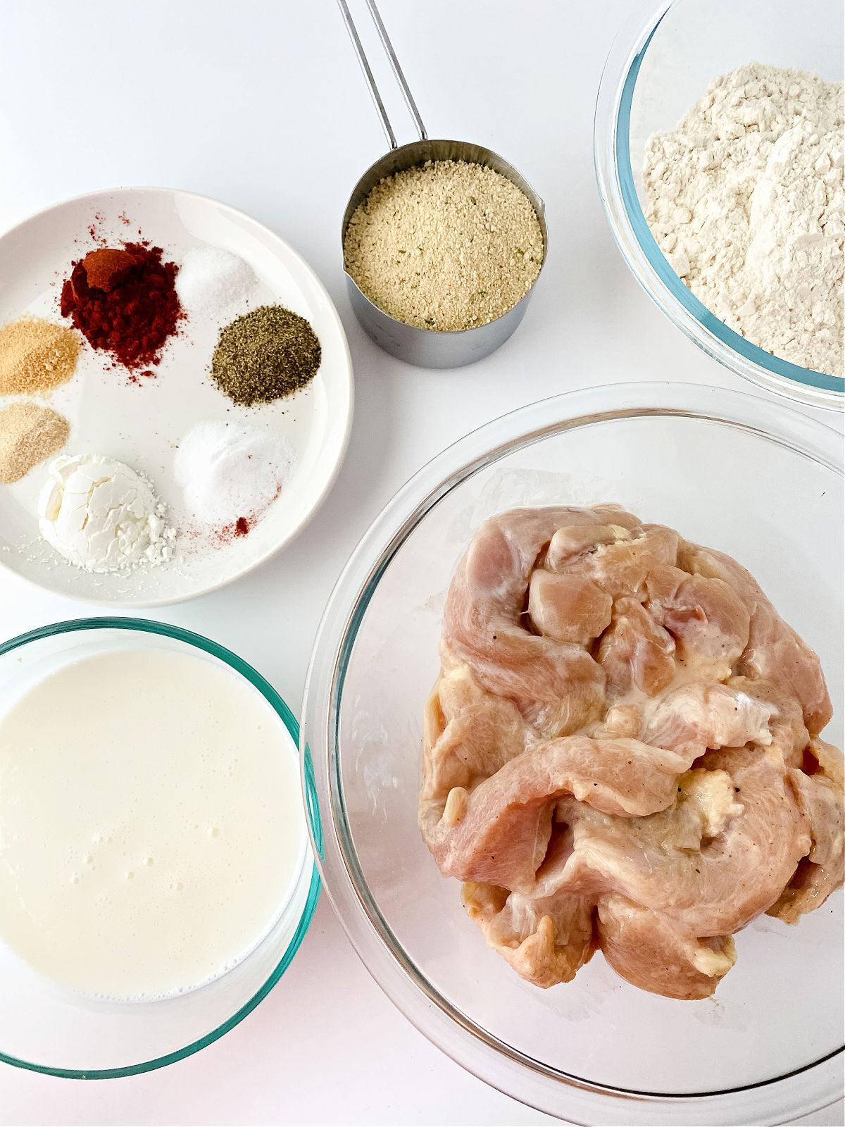 Sliced chicken breasts, seasoning, buttermilk, and breadcrumbs.