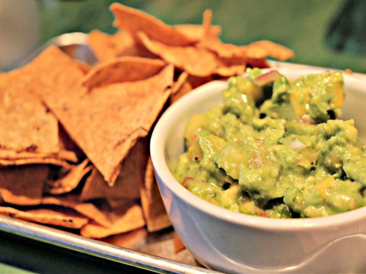 Bowl of fresh guacamole and a side of tortilla chips.