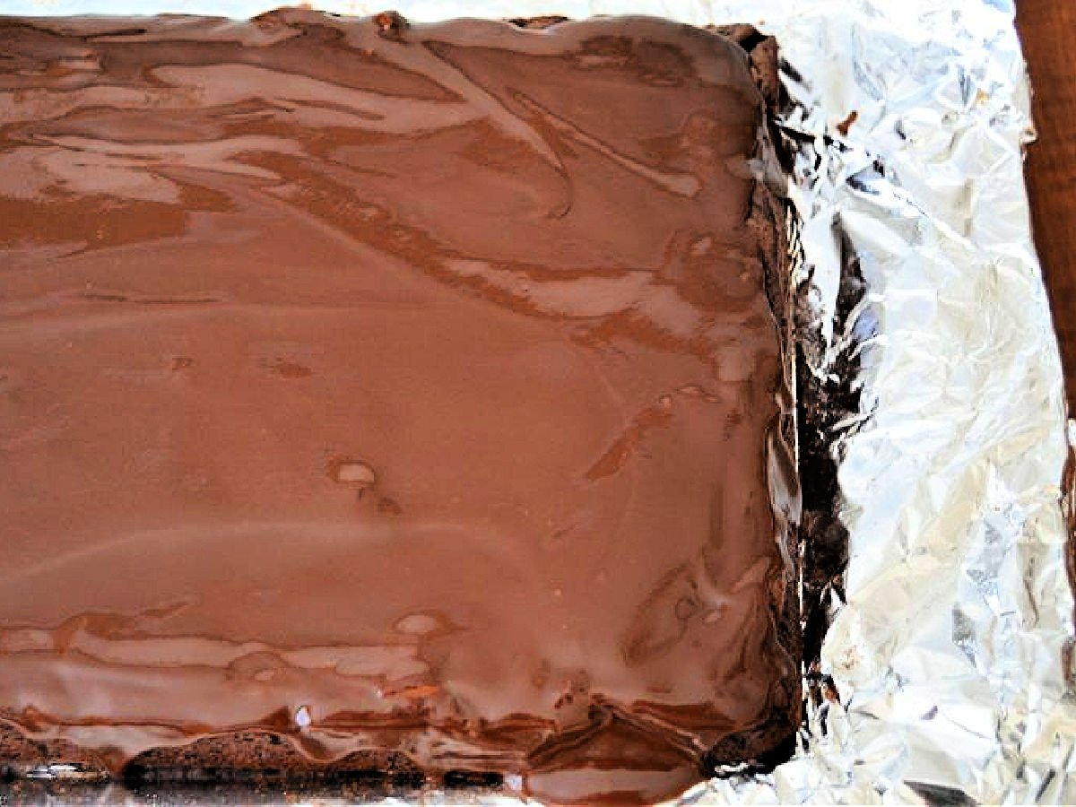 Iced brownie cake in a foil lined baking pan.