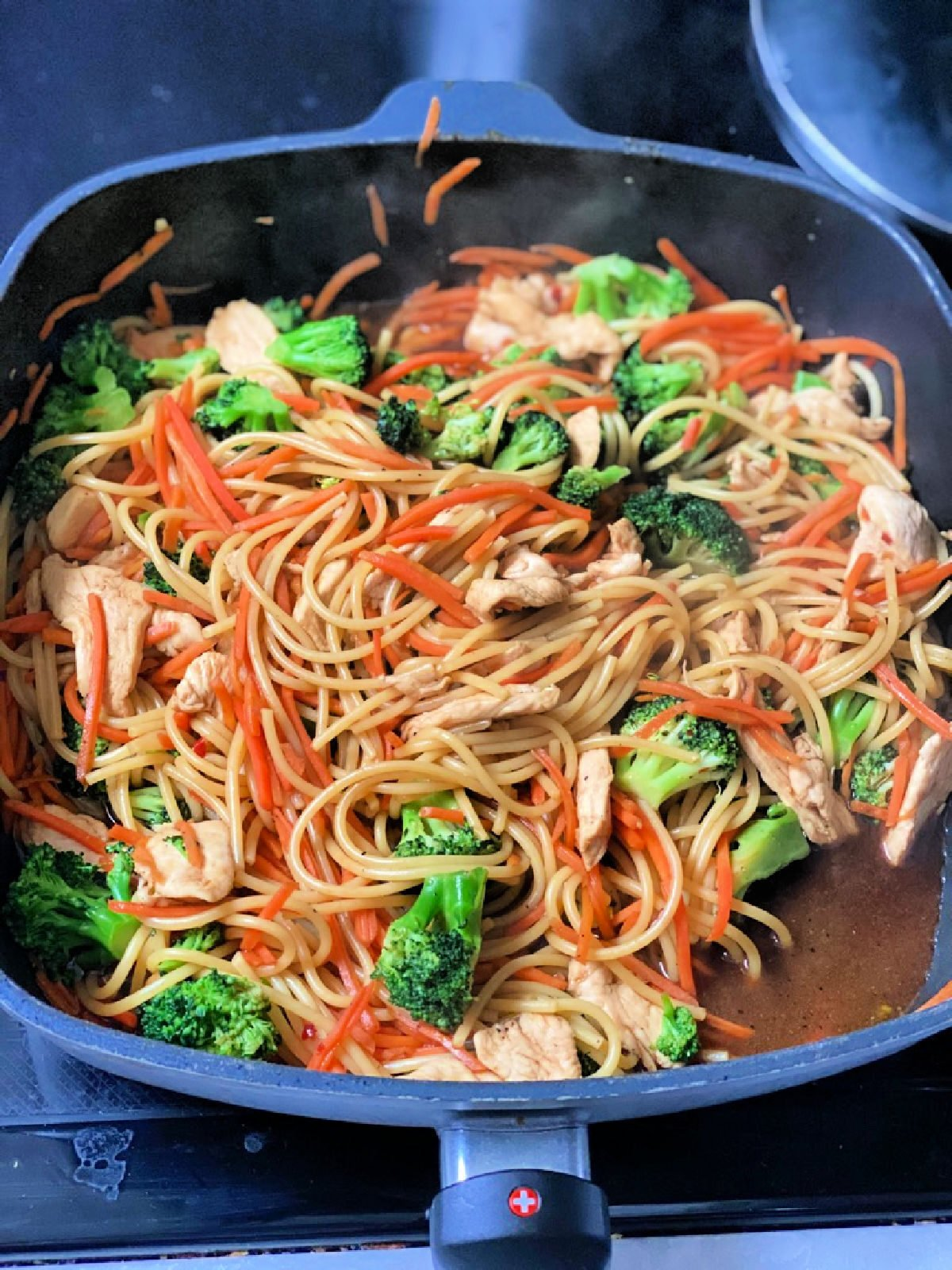 Spaghetti noodles, lo mein seasoning, broccoli, and shredded carrots in a skillet.