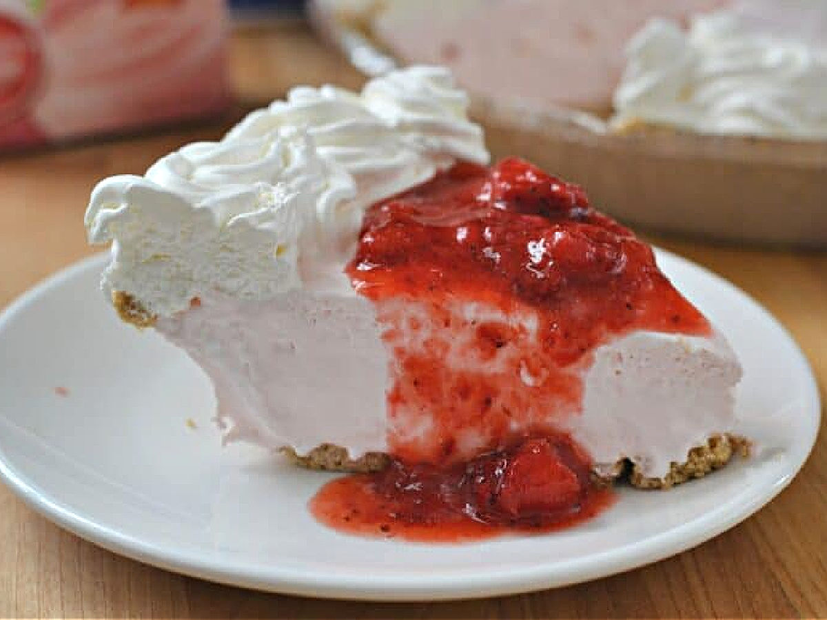 Slice of strawberry pie topped with strawberry jam on a white plate.