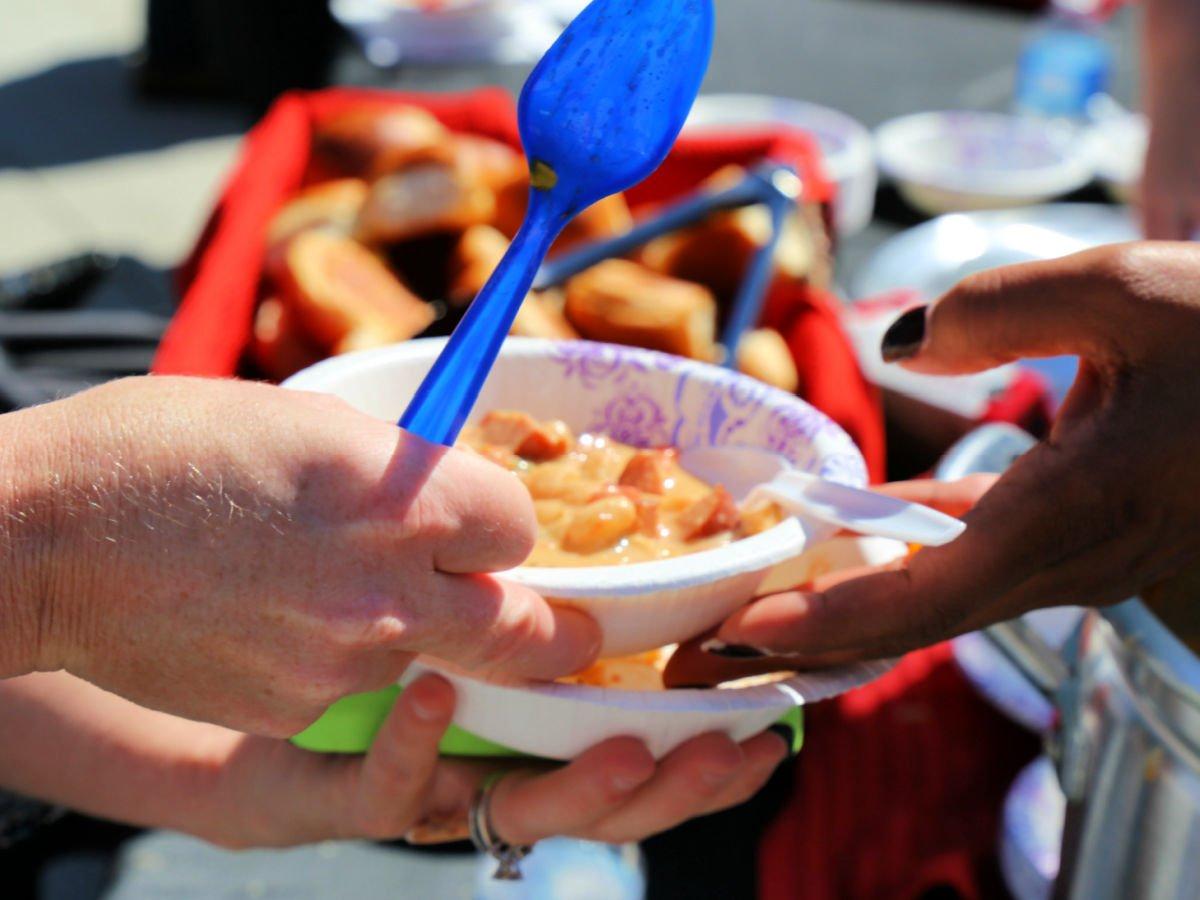 Black person handing a white person a bowl of cajun chili.