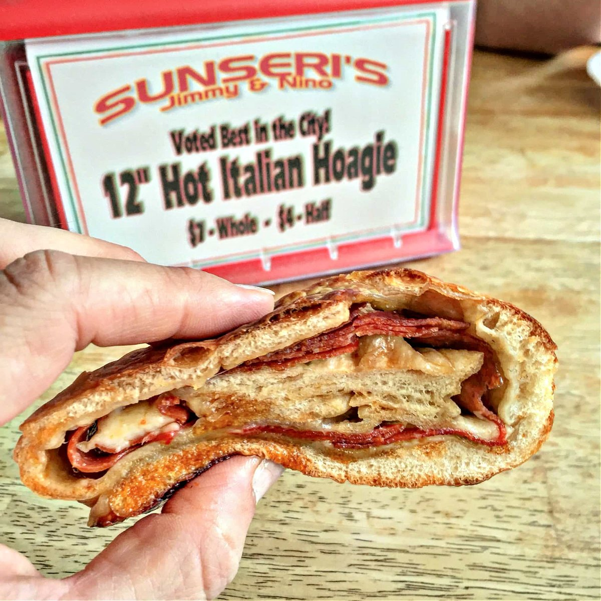 Woman's hand holding pepperoni Stromboli roll from Sunseri's.