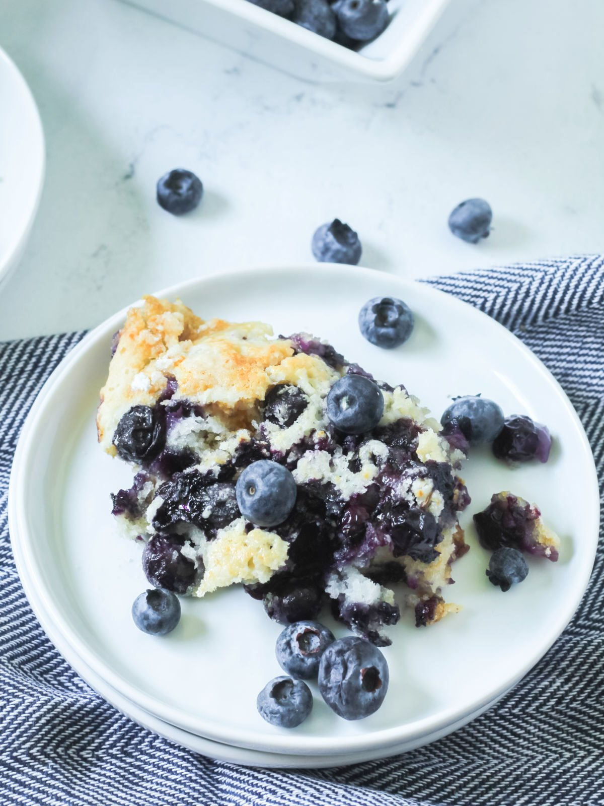 Blueberry cobbler topped with fresh blueberries on a white plate.