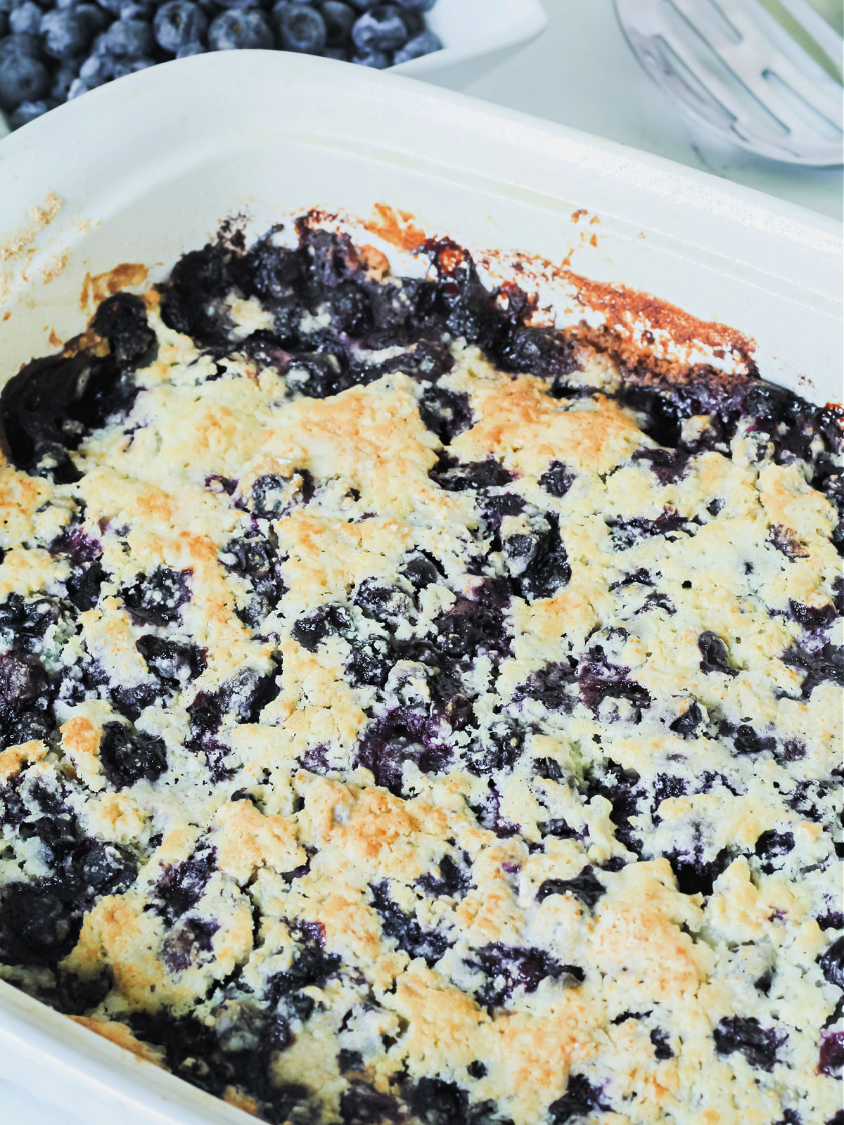 Baked blueberry cobbler in a white baking dish.