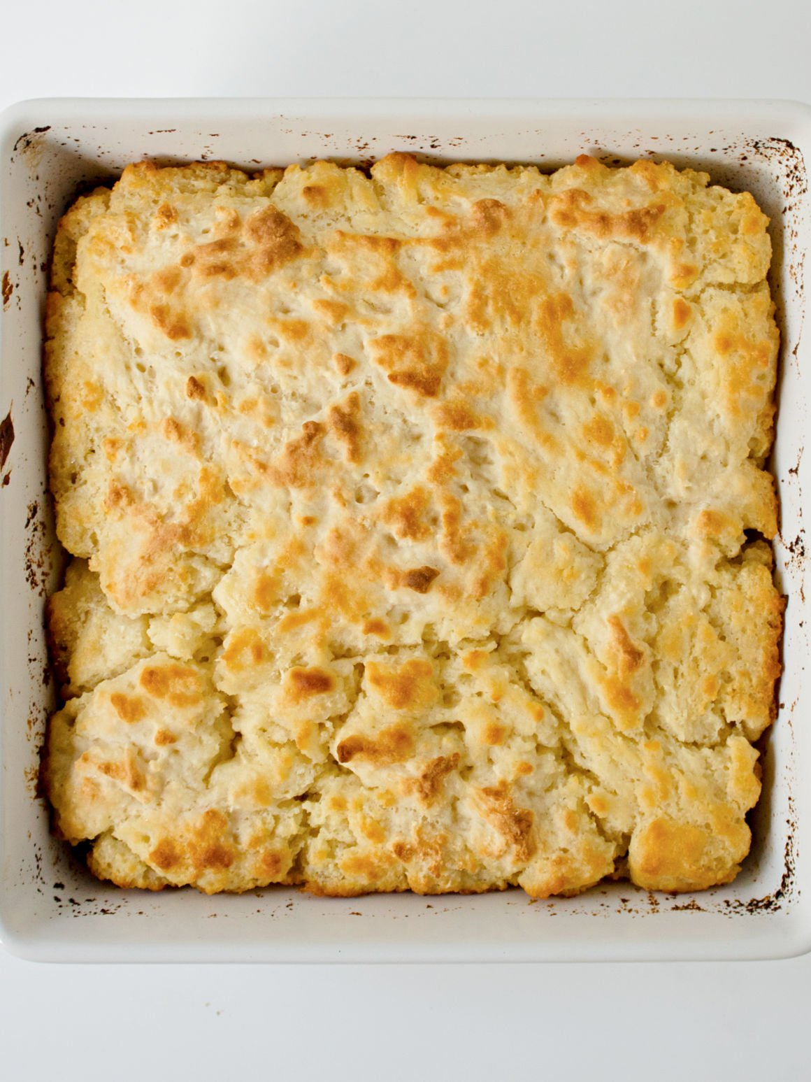 White baking pan filled with baked butter swim biscuits.