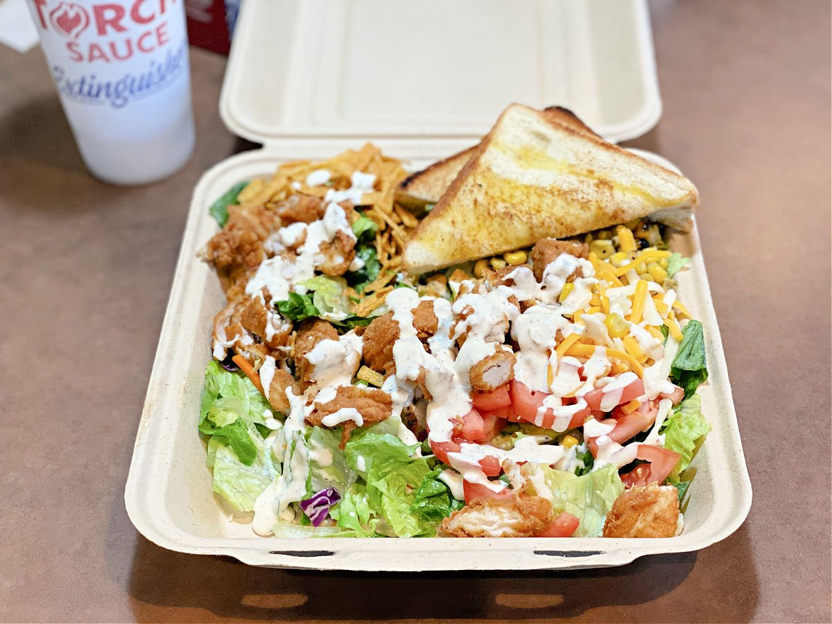 Zaxby's southwest salad with tomatoes, corn, lettuce, fried chicken, and Texas toast.