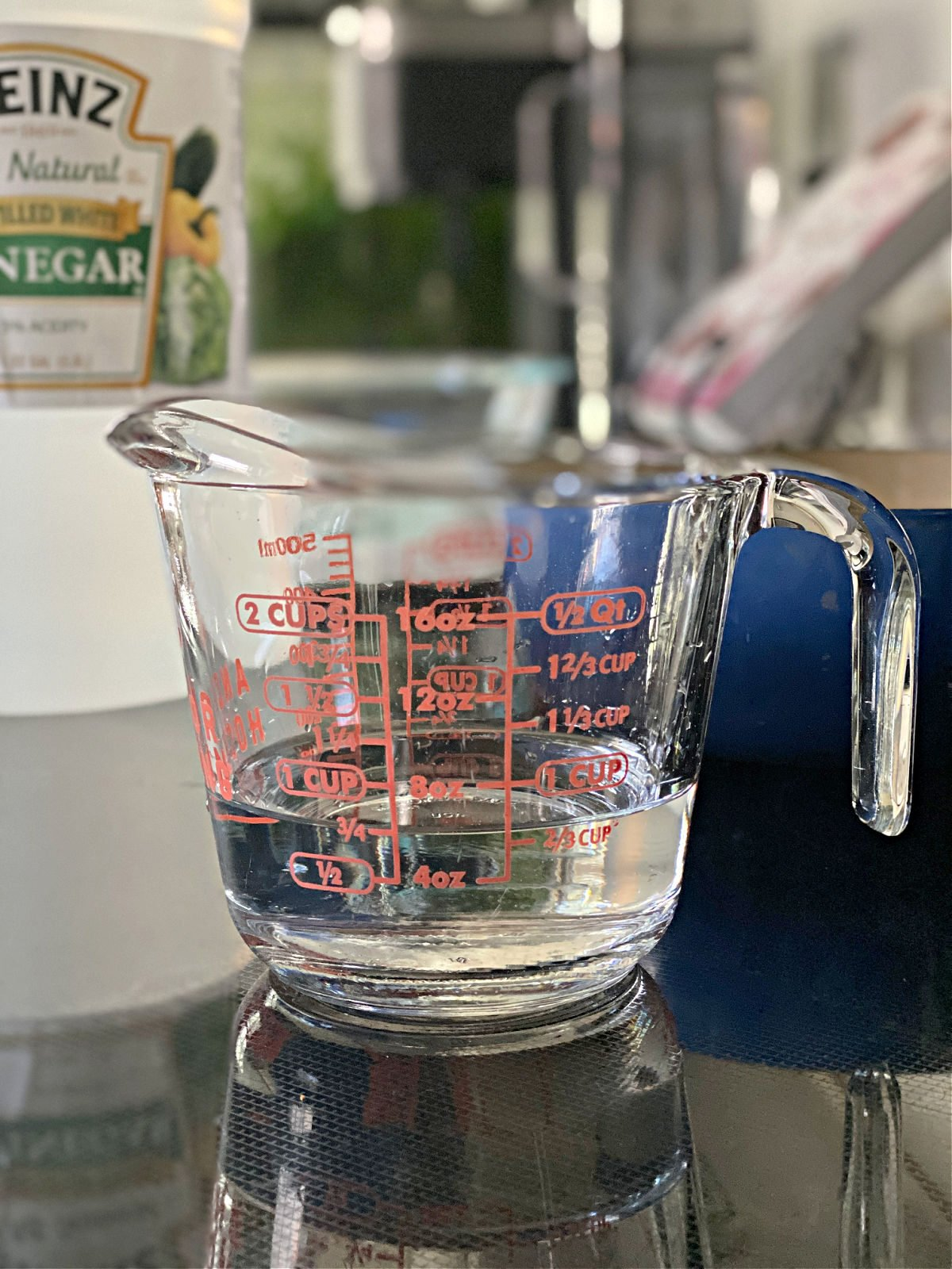 Measuring cup with vinegar on a black surface.
