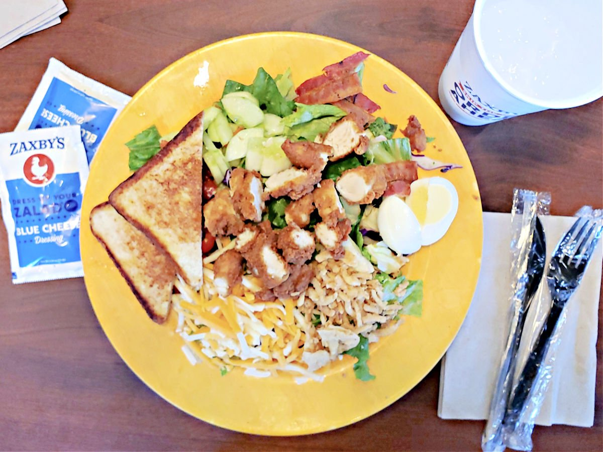 Zaxby's Cobb salad on a yellow plate with Texas toast and plastic utensils.