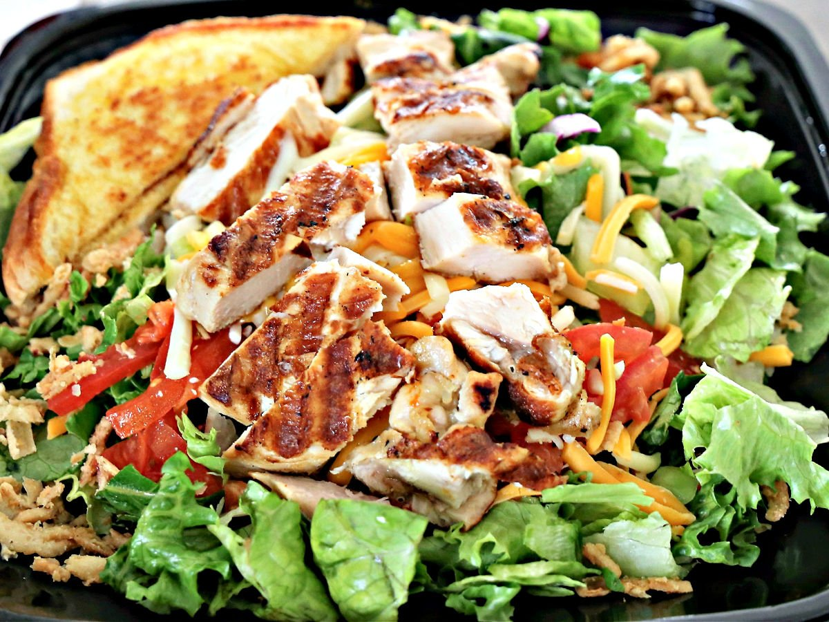 Zaxby's grilled house salad in a to-go container with Texas toast.