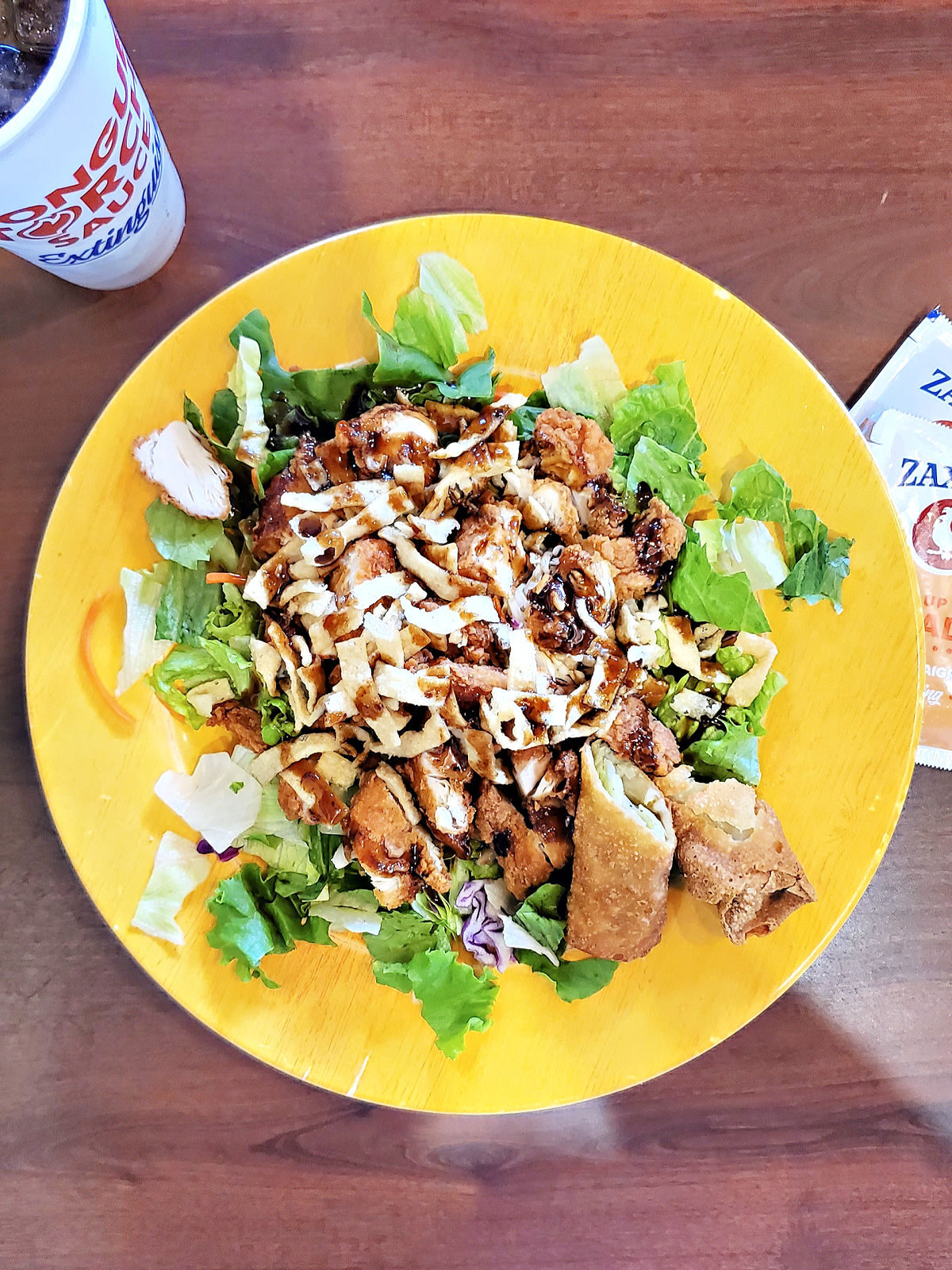 Zaxby's Zensation salad on a yellow plate served with an eggroll.