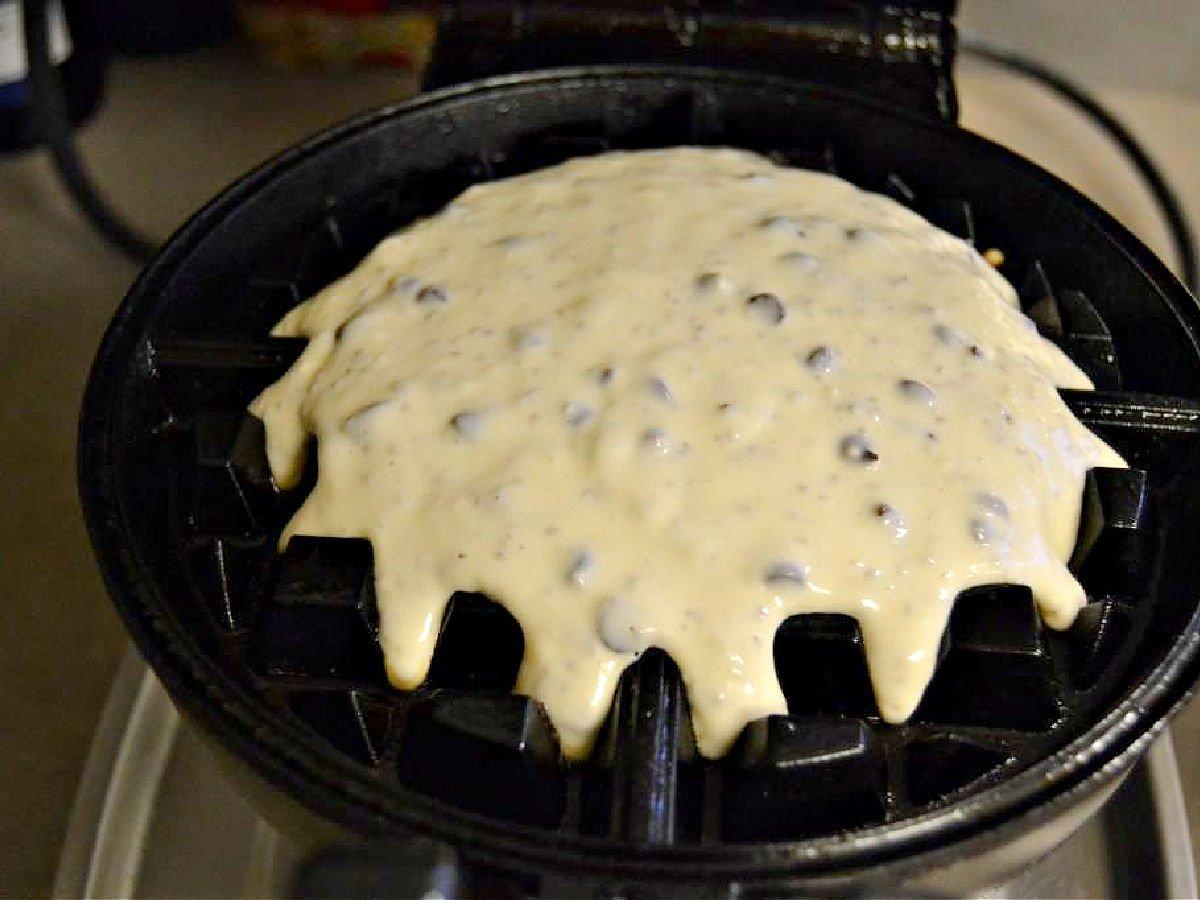 Chocolate chip waffle batter on a hot waffle iron.