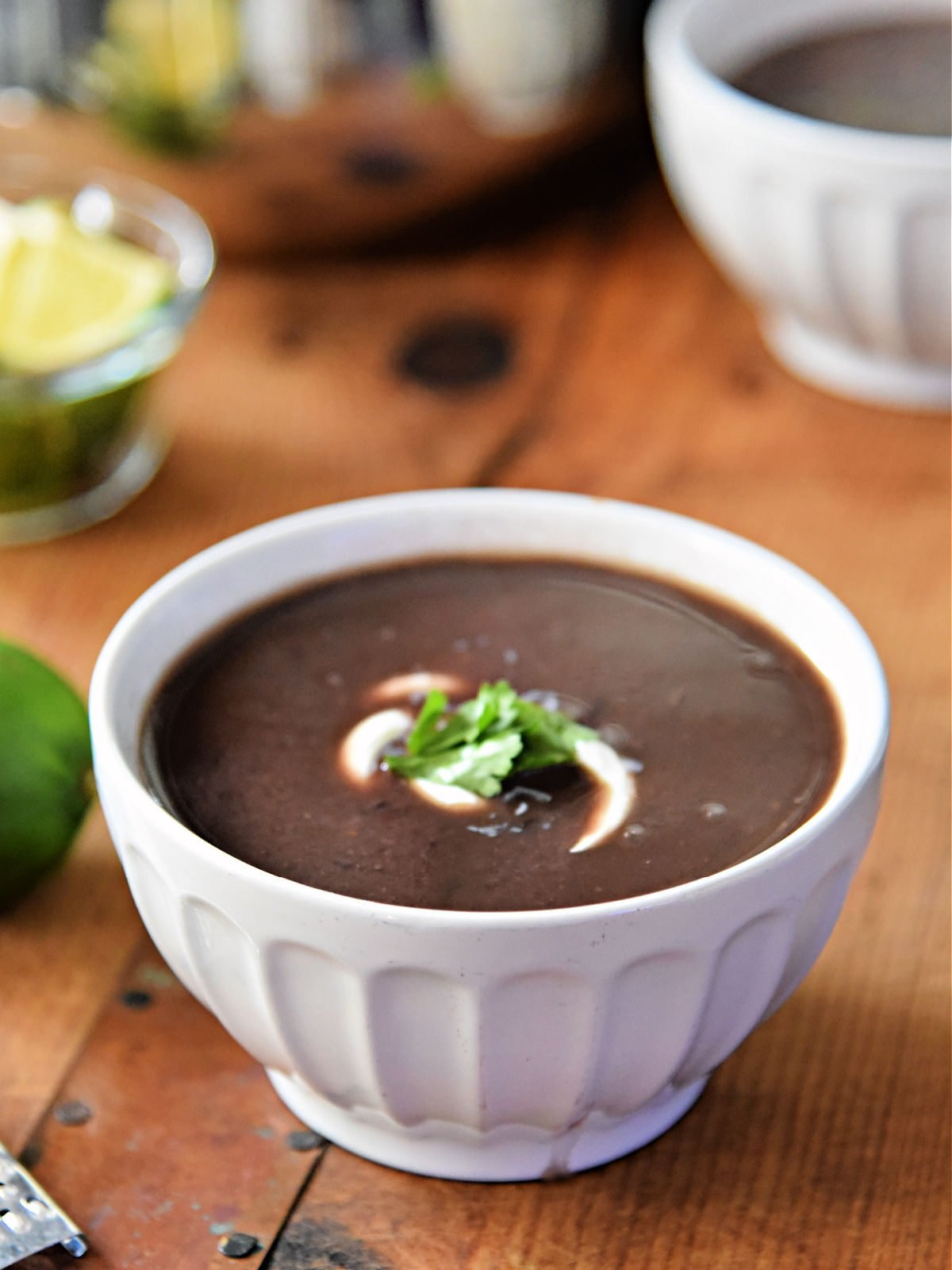 White bowl filled with black bean soup topped with sour cream and cilantro.