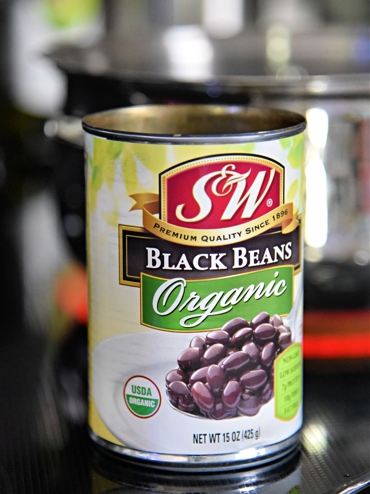 Can of organic black beans near a large soup pot.