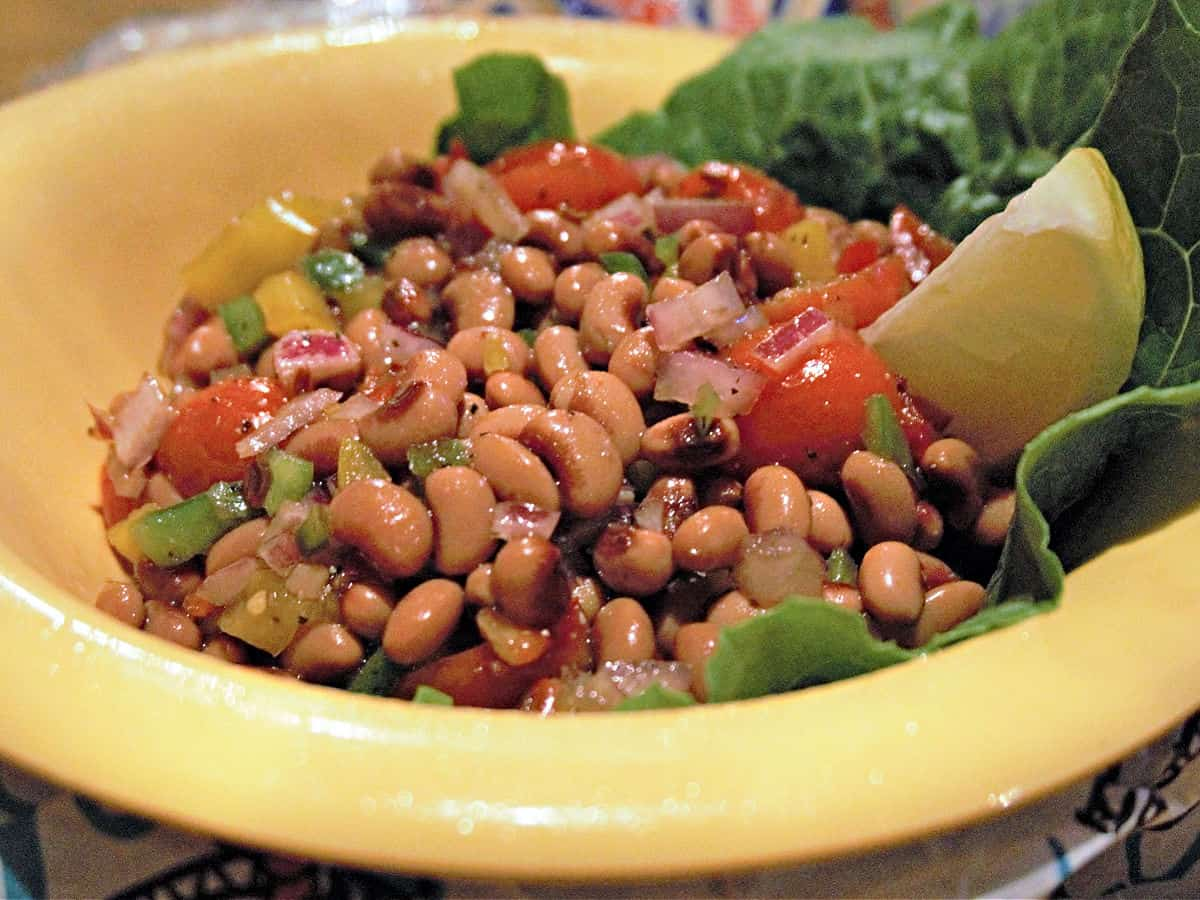 Yellow bowl filled with black-eye peas and lemon wedge.