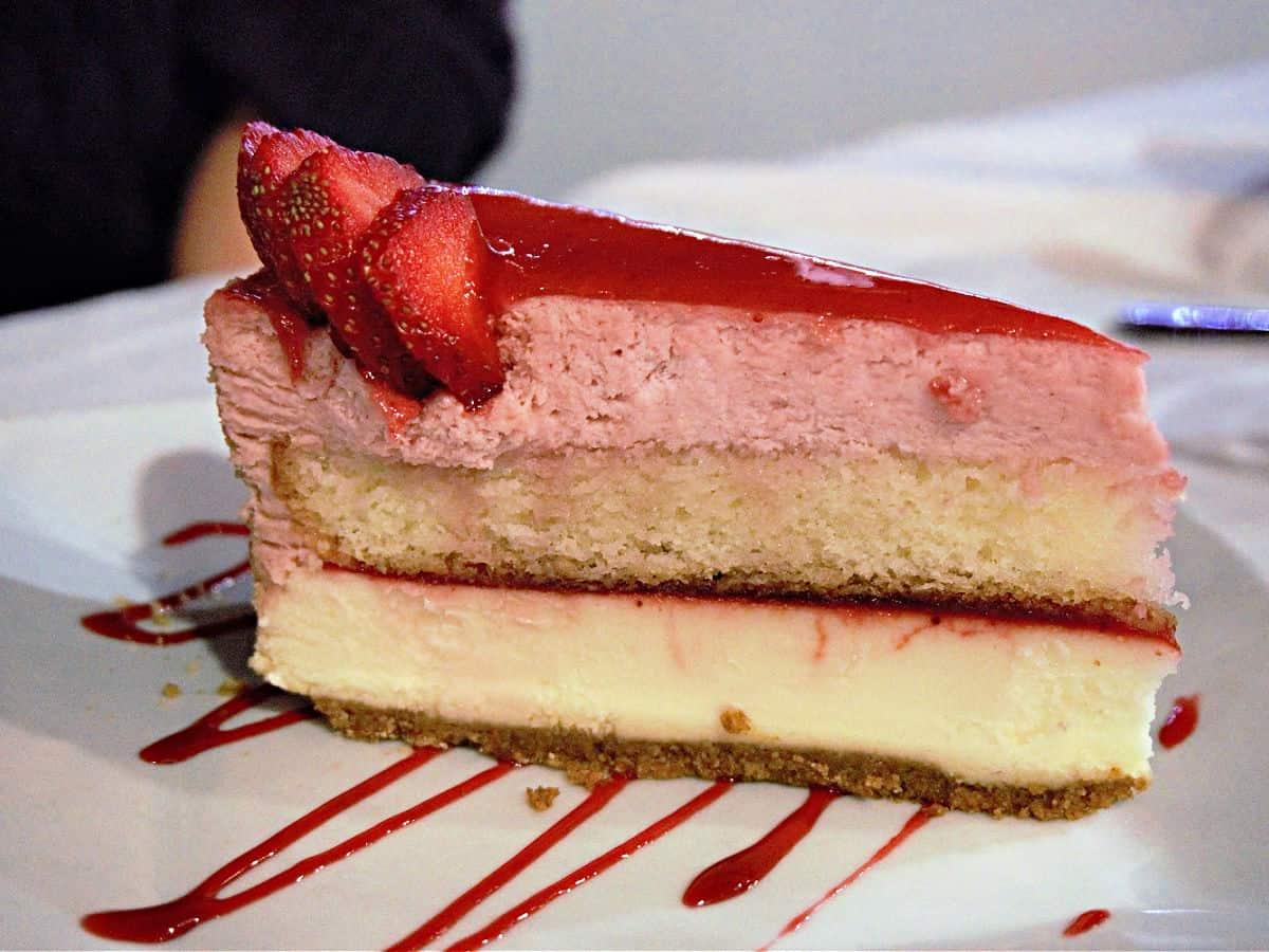 Slice of layered strawberry cheesecake.