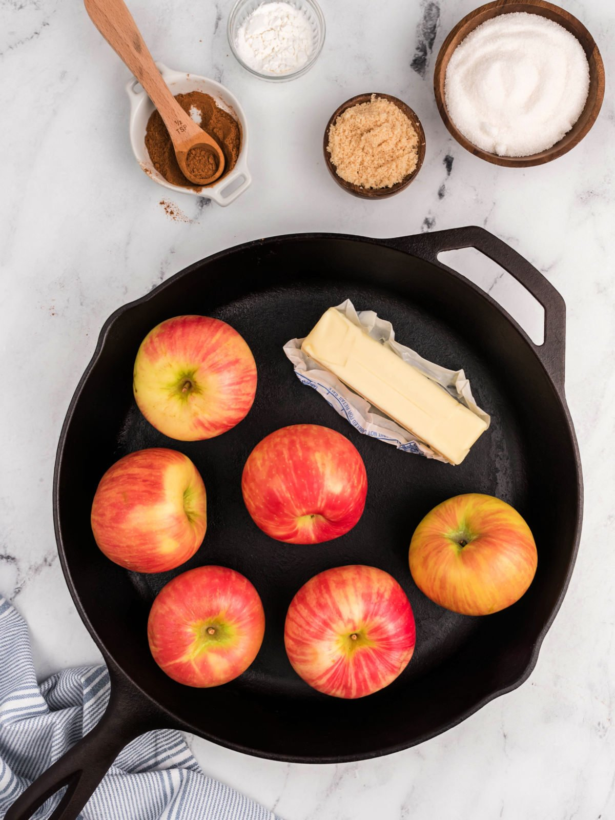 Cast iron skillet with six apples and a stick of butter.