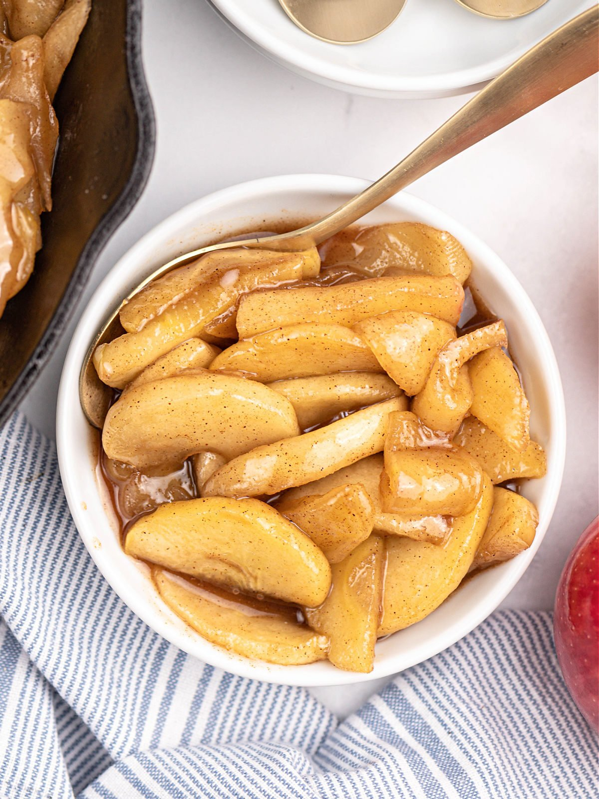 Bowl of fried apples and metal spoon.
