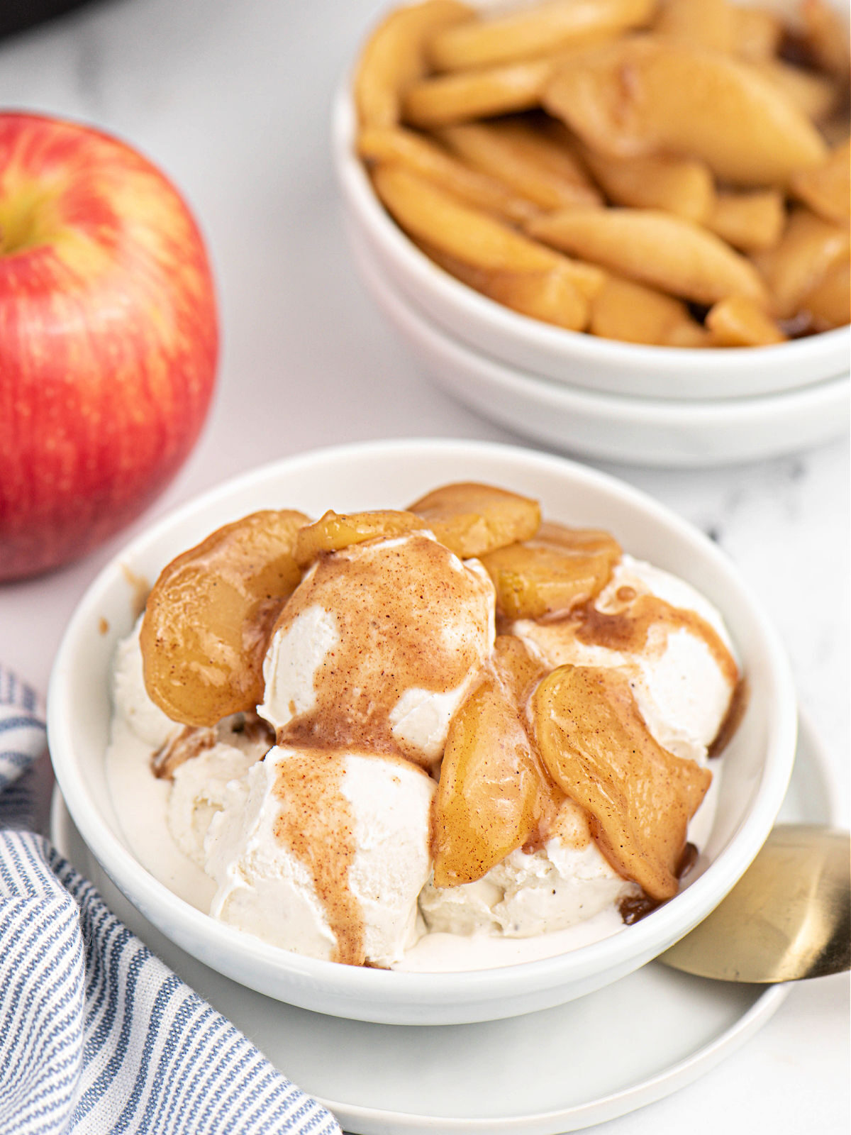 Vanilla ice cream with fried apples in a white bowl.