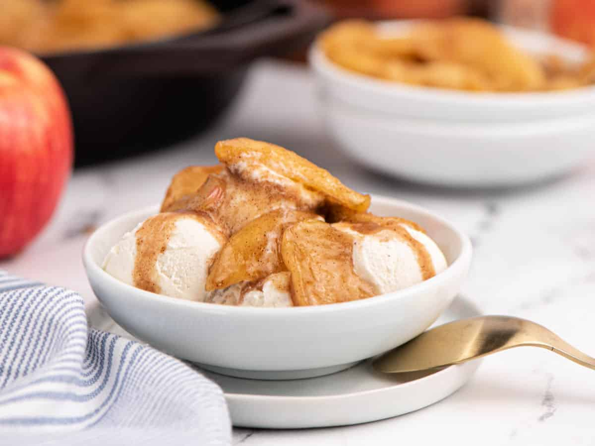 White bowl with vanilla ice cream topped with fried apples.
