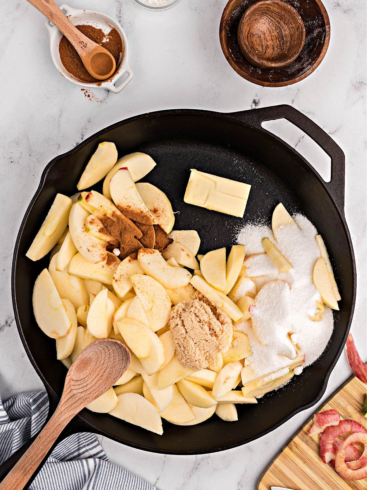 Cast iron skillet with apple slices, sugar, and spices.