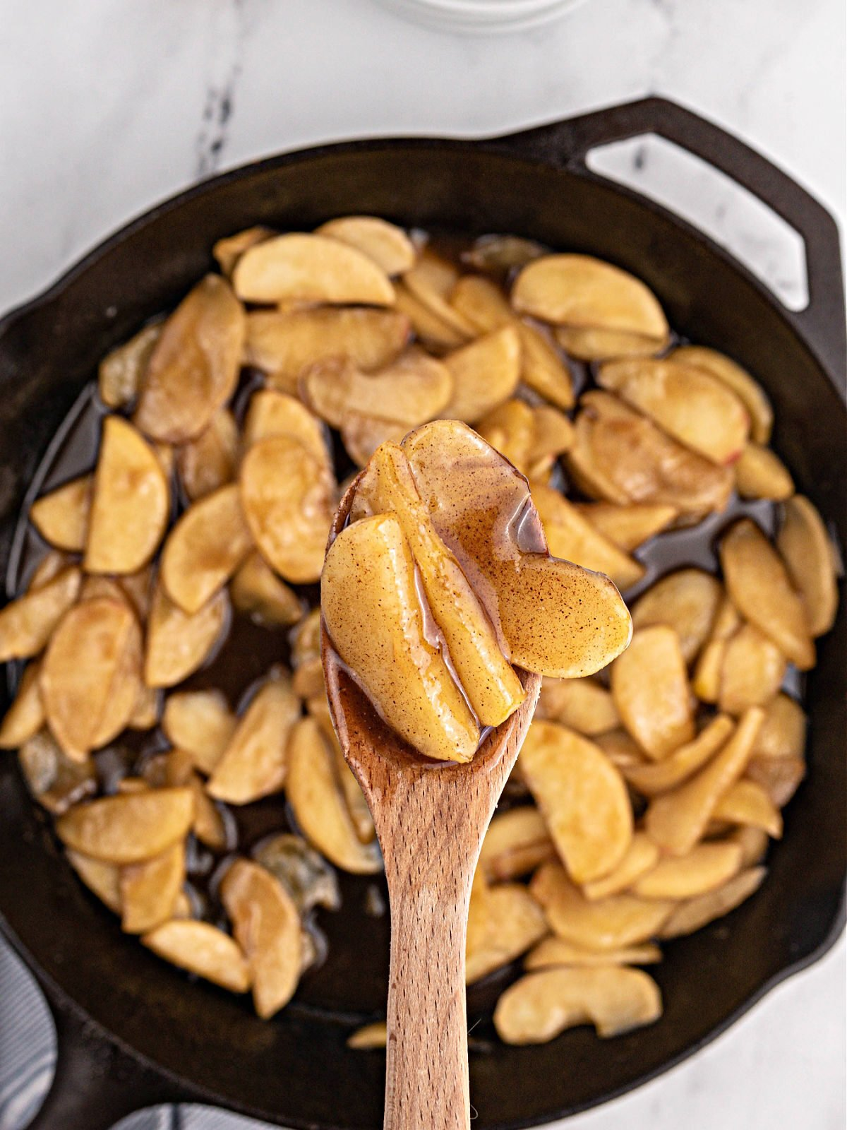 Wooden spoon holding fried apple slices over a cast iron skillet.