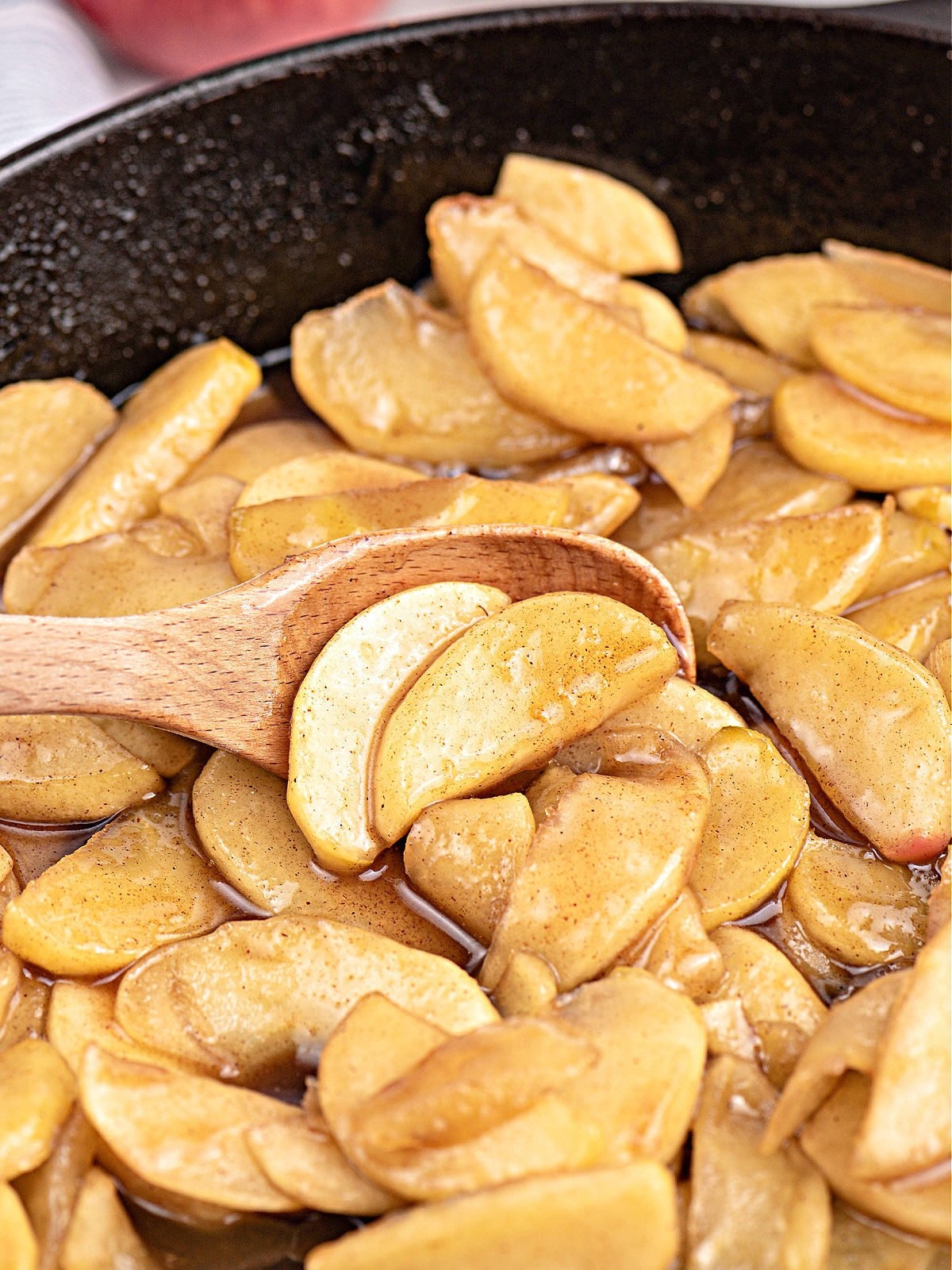 Wooden spoon stirring fried apples in a cast iron skillet.