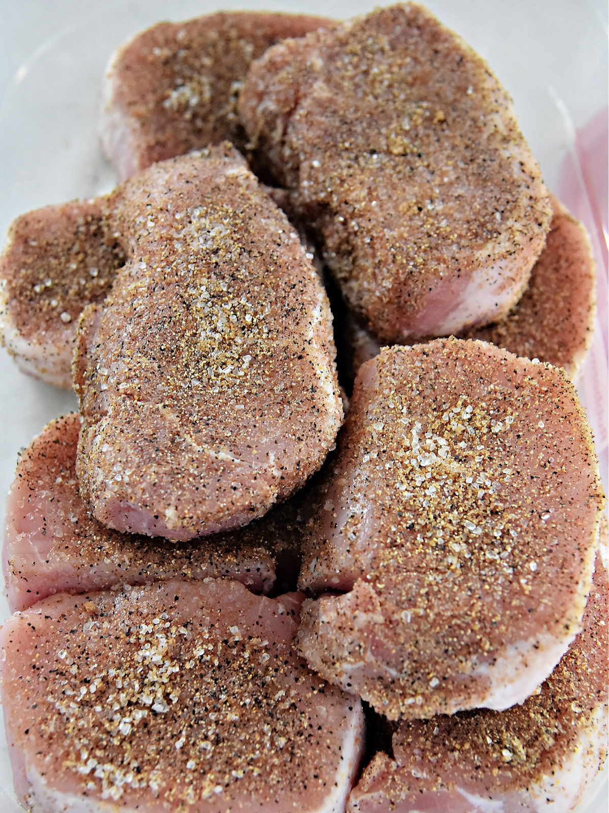 Raw pork chops covered in seasoning blend in a plastic container.