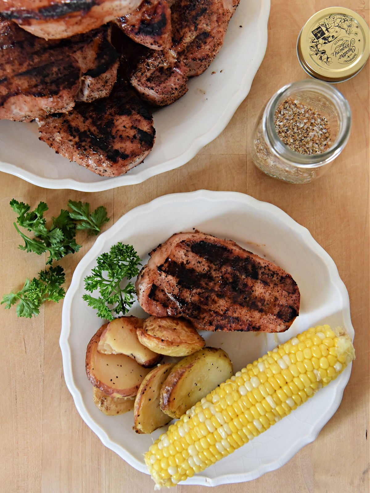 Grilled pork chop, potatoes, and corn on a white plate.