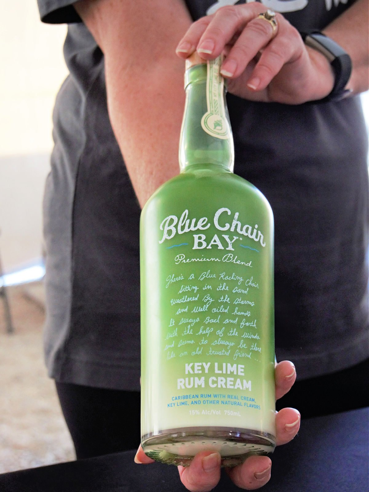 Lady holding a bottle of Blue Chair Bay Key Lime Rum Cream.