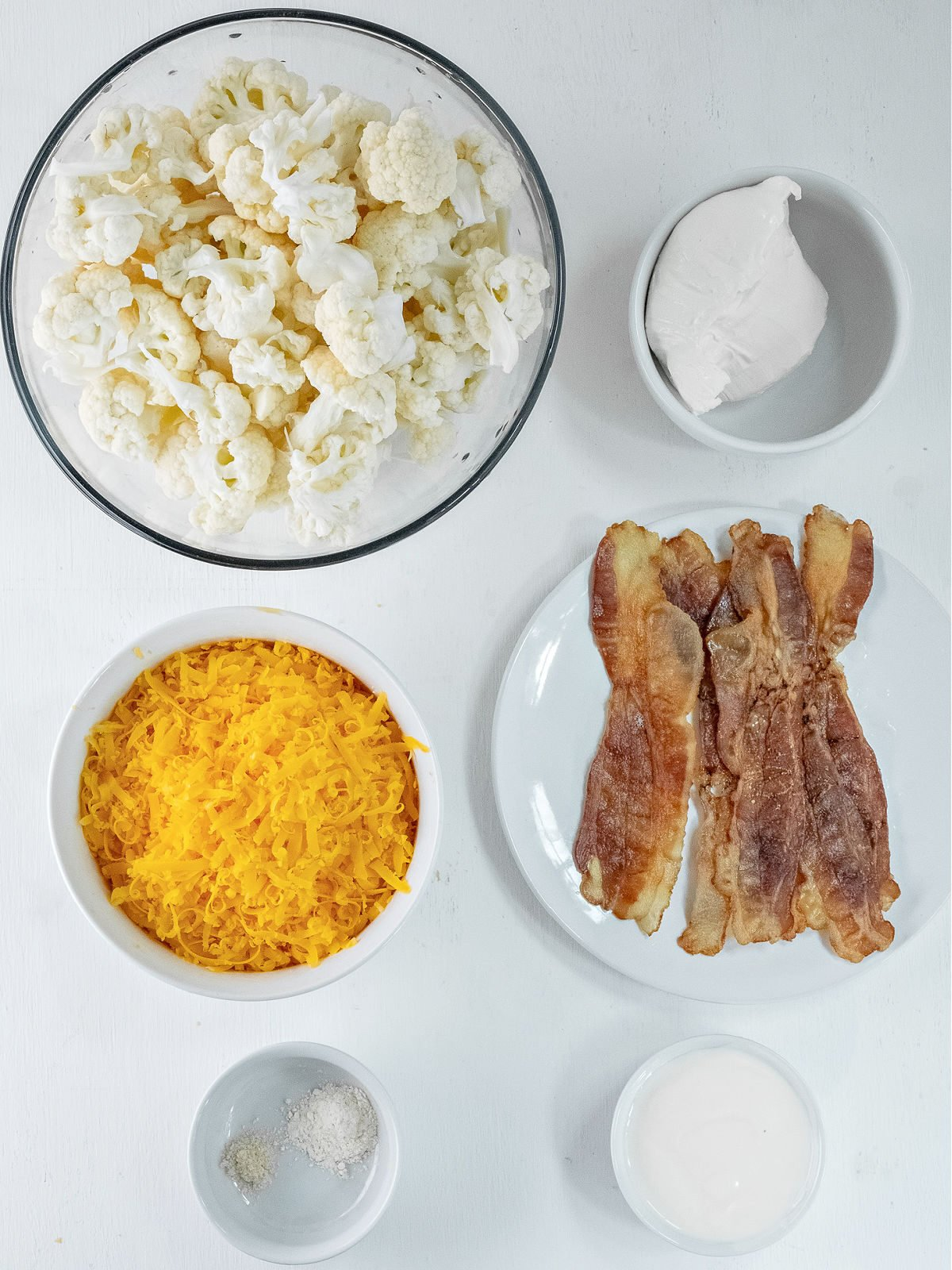 Bowl of cauliflower, bowl of Cheddar cheese, ramekin with cream cheese, plate of bacon, and ramekins of seasonings.