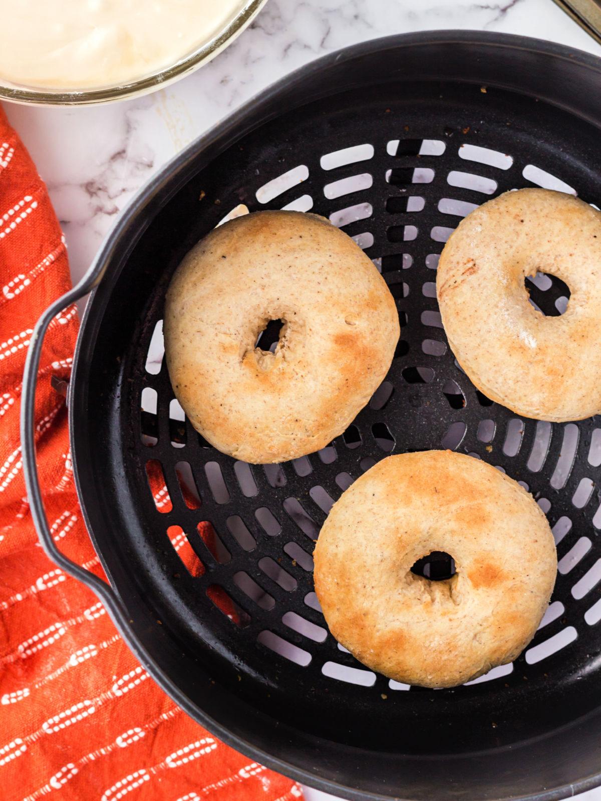 Three doughnuts in an air fryer basket.