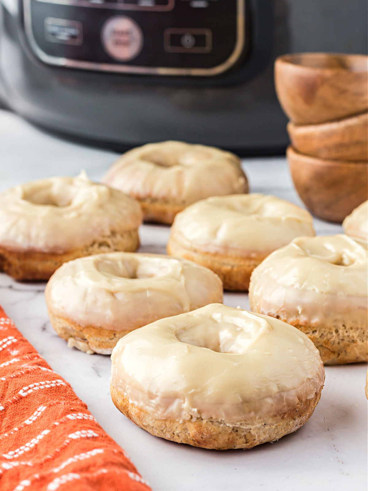 Glazed maple doughnuts in front of an air fryer.