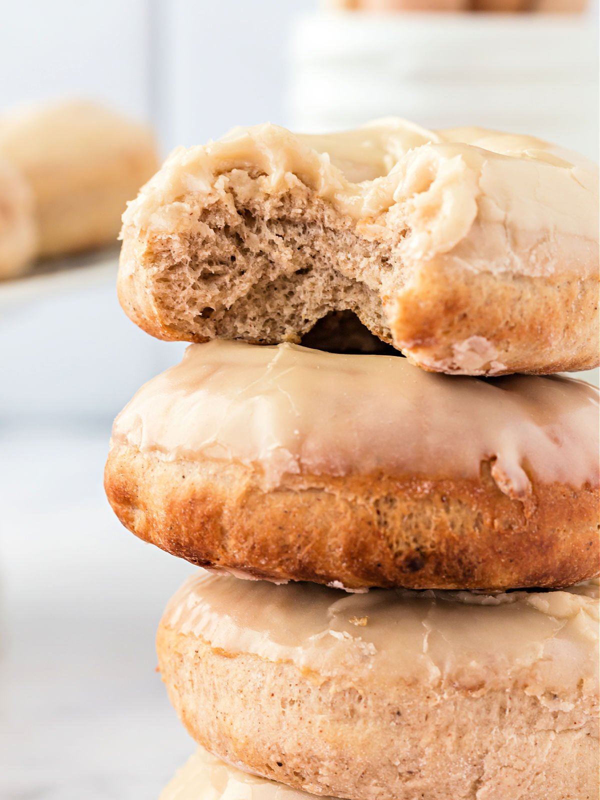 Stack of glazed maple doughnuts with top doughnut missing a bite.