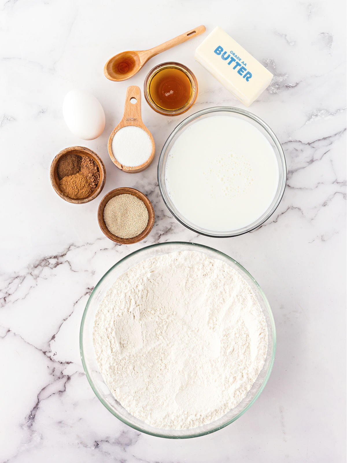 Flour, milk, yeast, spices, maple syrup, and butter on a marble counter.