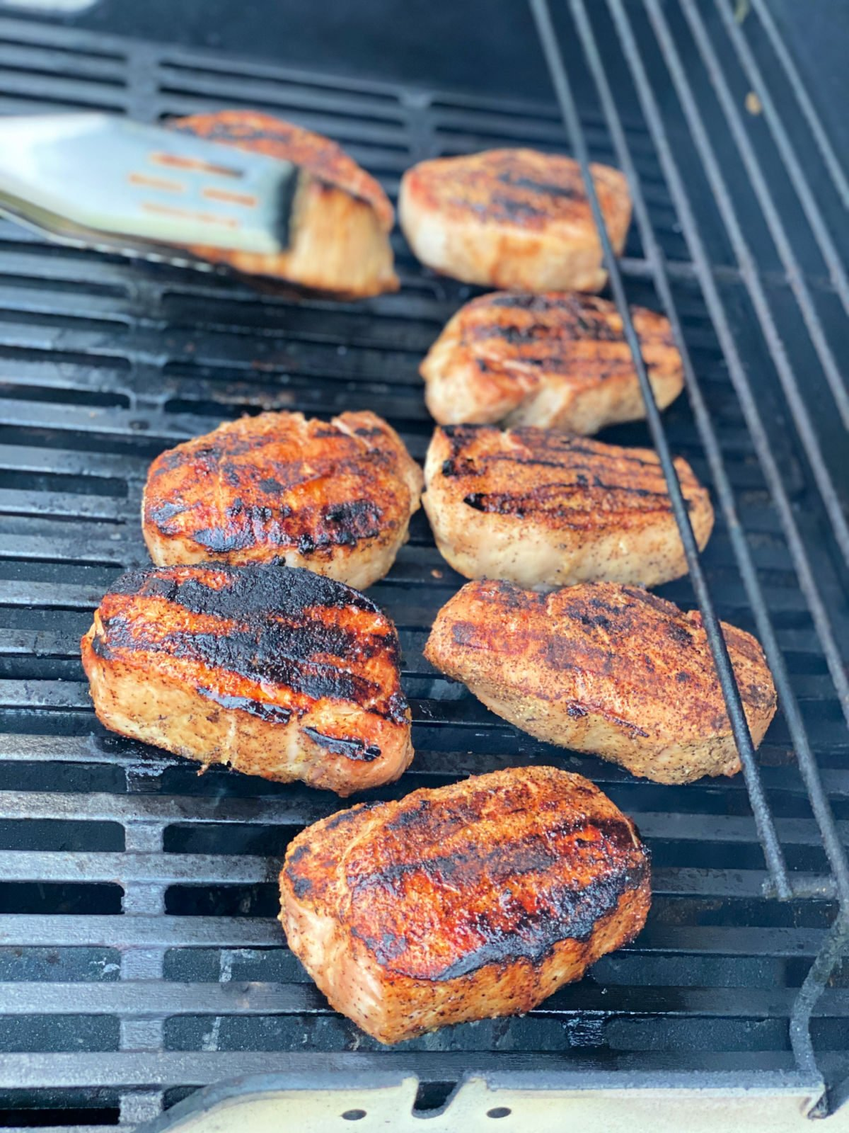 Nine pork chops cooking on a gas grill.